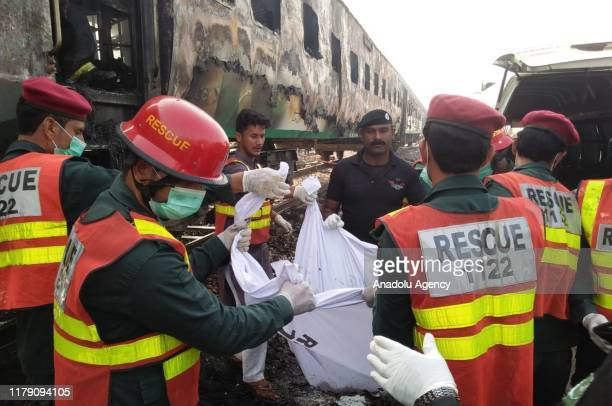Pakistani rescuers shift a victim from a train as fire erupted in it in a gas cylinder blast at Chani Goth area in Rahimyar District in southern...