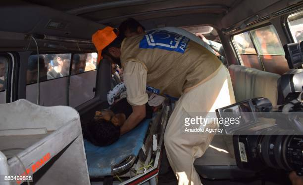 Pakistani rescuers shift an injured victim in a ambulance to take him to hospital following an attack on Peshawar Agricultural Training Institute by...