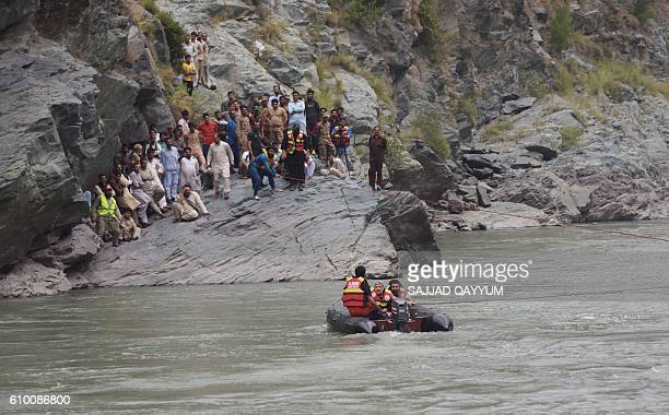 Pakistani rescuers use ropes attached to a crane to try to recover a bus that fell into a river in Nausehri some 45 kilometres north of Muzaffarabad...