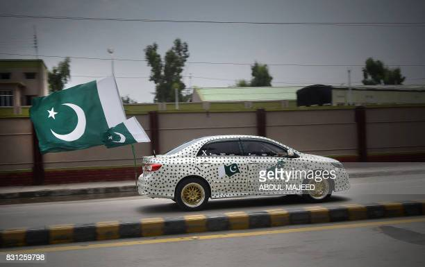 Pakistani resident drives his car decorated with national flags to mark the country's Independence Day in Peshawar on August 14 2017 This month marks...