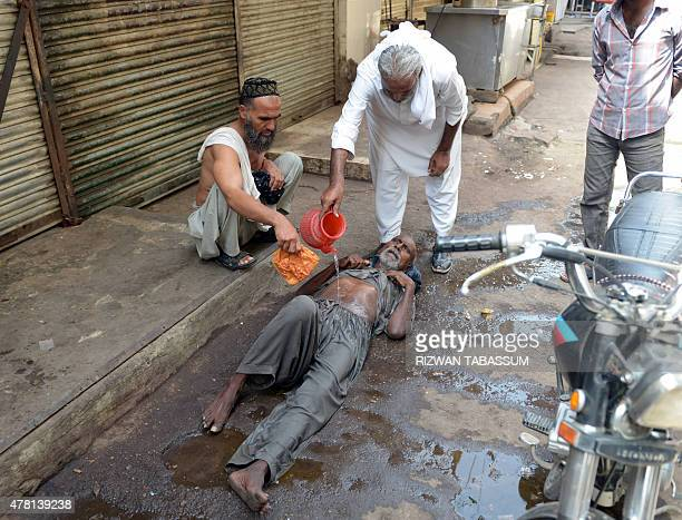 A Pakistani resident helps a heatstroke victim at a market area during a heatwave in Karachi on June 23 2015 The death toll from a heatwave in...