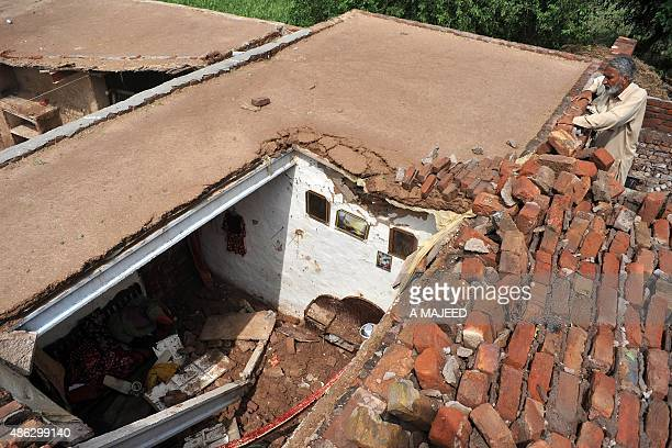 A Pakistani resident looks at his damaged house following heavy rain in Peshawar on September 3 2015 AFP PHOTO / A MAJEED