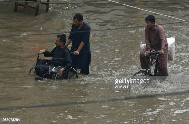 A Pakistani resident pushes a wheelchair carrying a man through a flooded street during heavy rains in Lahore on June 29 2018