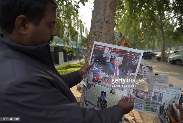 A Pakistani resident reads a newspaper with coverage of Donald Trump's victory in the US presidential election in Islamabad on November 10 2016 / AFP...