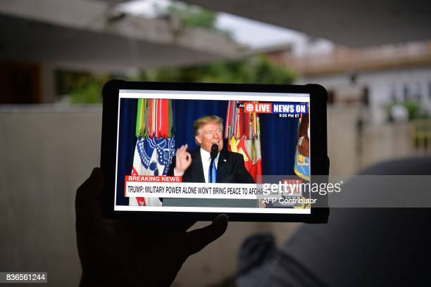 A Pakistani resident watches his tablet device in Islamabad on August 22 showing a live broadcast of US President Donald Trump delivering his address...