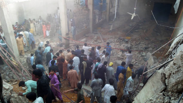 TOPSHOT - Pakistani residents and volunteers search for victims in