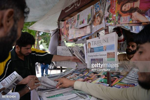 Pakistani residents buy newspapers with front page headlines about US President Donald Trump at a stall in Islamabad on August 23 2017 Angry and...