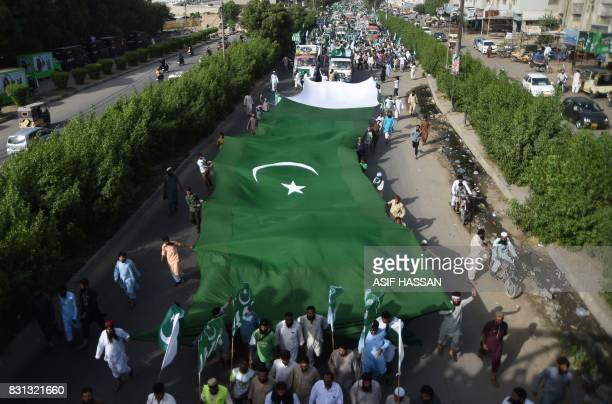 Pakistani residents carry a huge flag during a rally to mark the country's Independence Day in Karachi on August 14 2017 This month marks 70 years...