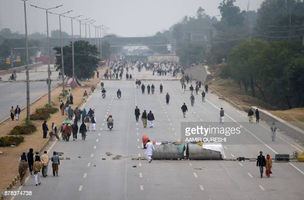 Pakistani residents cross a blocked highway by activists of the TehreekiLabaik Yah Rasool Allah Pakistan religious group during a protest in...