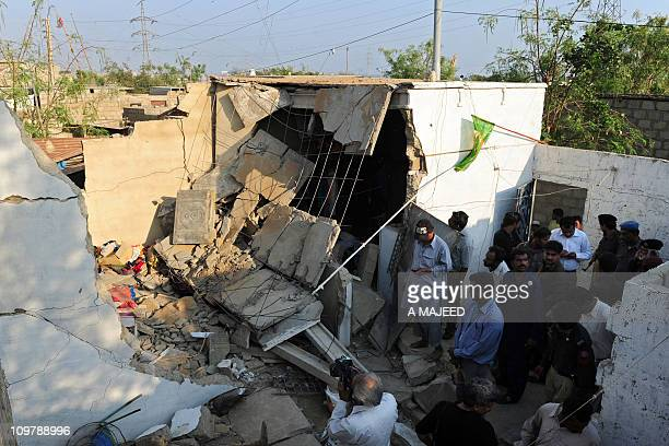 Pakistani residents gather at a bomb blast site in Karachi on March 5 2011 At least one person was killed and another wounded when a bomb exploded...
