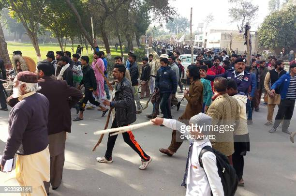 Pakistani residents hold bamboo sticks as they stage a protest against the rape and killing of a girl in Kasur in Punjab province on January 10 2018...