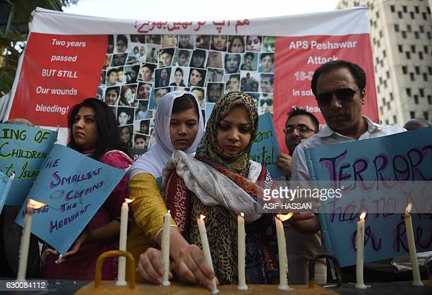 Pakistani residents hold lighted candles during a ceremony in Karachi on December 16 as they pay tribute to victims on the second anniversary of an...