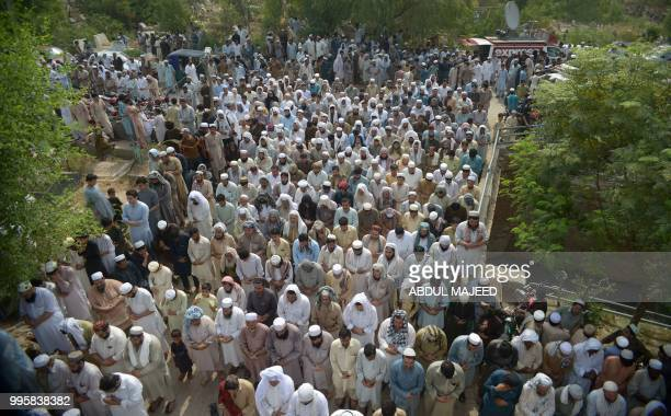 Pakistani residents offer funeral prayers for blast victims who were killed in a suicide bombing at an election rally during their funeral in...