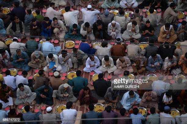 Pakistani residents offer prayers before breaking their fast along a street in Rawalpindi on May 29 2017 Muslims throughout the world are marking the...