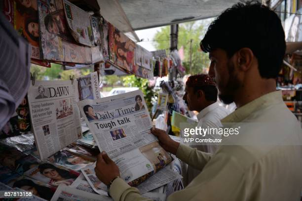 Pakistani residents read newspapers with a front page headline about US President Donald Trump at a stall in Islamabad on August 23 2017 Angry and...