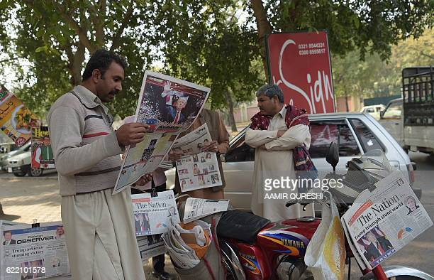 Pakistani residents read newspapers with coverage of Donald Trump's victory in the US presidential election in Islamabad on November 10 2016 / AFP /...
