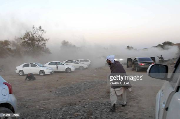 Pakistani residents run following a bomb blast in Bannu on November 26 2015 At least two people were killed when a roadside bomb hit the convoy of a...