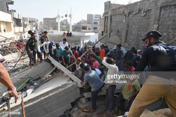 Pakistani residents search for victims in the rubble of a collapsed three storey residential building in Karachi on February 25 2019 At least two...