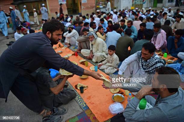 Pakistani residents serve Iftar food to break the Ramadan fast at a bus terminal in Peshawar on May 25 2018 Muslims throughout the world are marking...