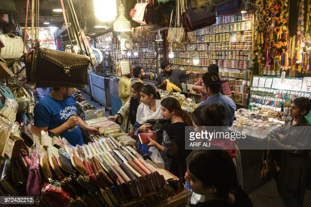 Pakistani residents shop at a market during holy month of Ramadan in Lahore on June 12 2018 Muslims around the world are preparing to celebrate the...