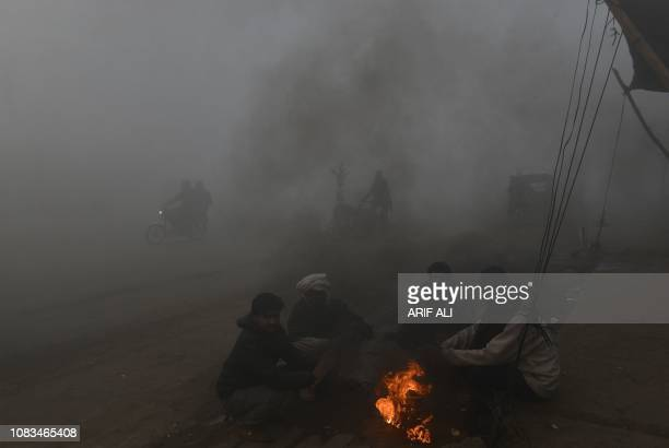 Pakistani residents sit around a wood fire alongside a road amid heavy fog and smog conditions in Lahore on January 17 2019 Smog levels spike during...