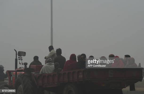 Pakistani residents travel on a tractor trolley amid heavy smog in Lahore on November 12 2017 Large swathes of Pakistan and north India see a spike...