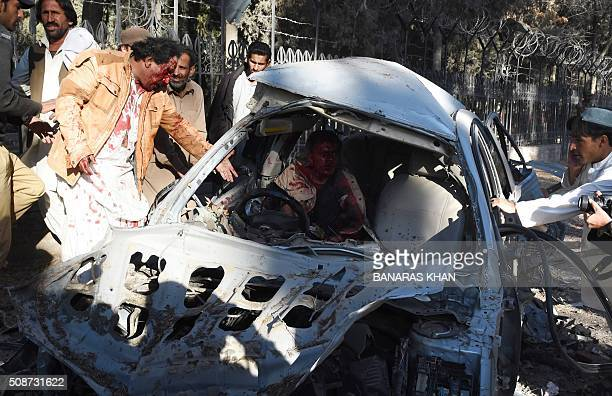 Pakistani residents try help an injured man trapped in a damaged car at the site of a bomb explosion that targeted a security convoy in Quetta on...