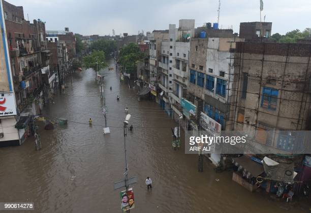Pakistani residents wade along a flooded street after heavy rains in Lahore on July 3 2018