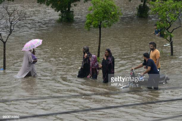 Pakistani residents wade through a flooded street during heavy rain in Lahore on July 3 2018