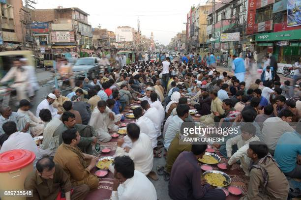 Pakistani residents wait to break their fast along a street in Rawalpindi on May 29 2017 Muslims throughout the world are marking the month of...