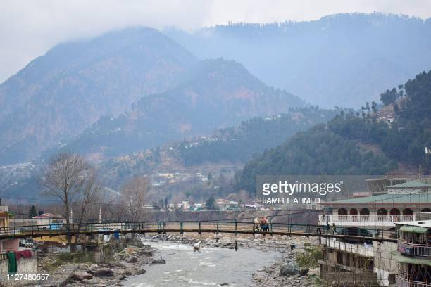 Pakistani residents walk on a bridge in the mountainous area of Balakot where the Indian Air Force launched a raid on February 26 2019 An air strike...