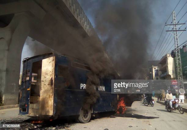 Pakistani residents walk past a burning prison van torched by protesters from the TehreekiLabaik Yah Rasool Allah Pakistan religious group during...