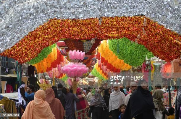 Pakistani residents walk through a decorated market for Eid MiladunNabi festival in Lahore on November 29 2017 Pakistani Muslims celebrate the birth...
