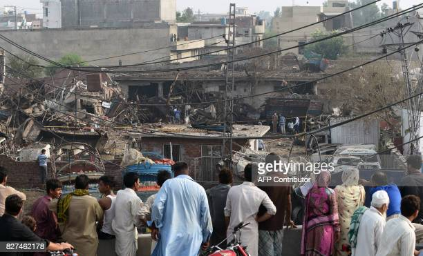 Pakistani residents watch the site following an overnight bomb explosion placed inside a truck in Lahore on August 8 2017 A truck bomb injured at...
