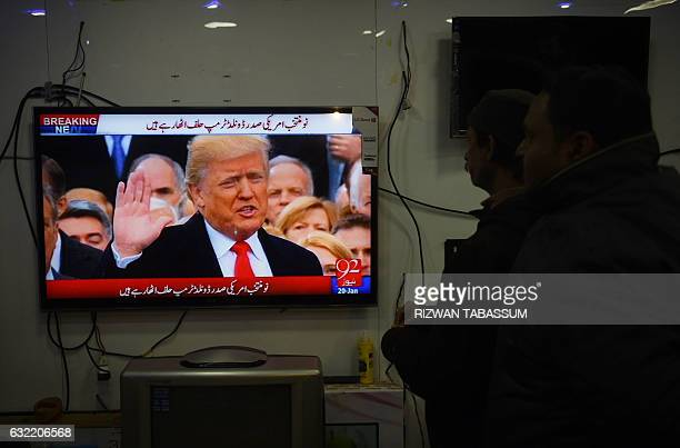 Pakistani residents watch the TV broadcast of the inaugural ceremony of new US President Donald Trump at a market in Karachi on January 20 2017...