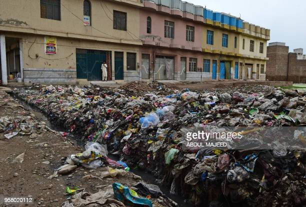 A Pakistani resients looks over a rubbish dump filled with plastic items in Peshawar on May 13 2018