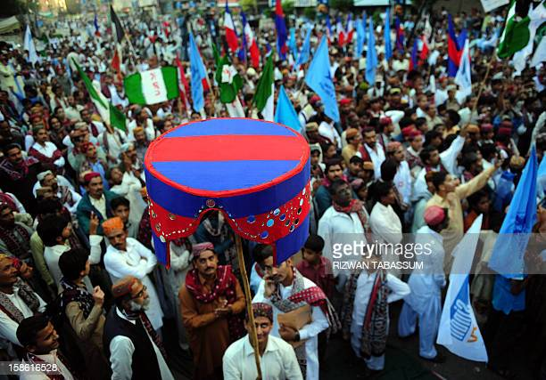 Pakistani revellers wearing traditional Sindhi cap and ajrak attire celebrate during a Sindh Cultural Day festival in Karachi on December 21 2012 The...