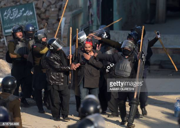 Pakistani riot policemen arrest an activist from the TehreekiLabaik Yah Rasool Allah Pakistan religious group during a clash in Islamabad on November...