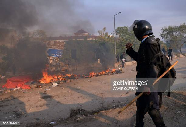 Pakistani riot policemen gather around the burning tents of protesters of the TehreekiLabaik Yah Rasool Allah Pakistan religious group in Islamabad...