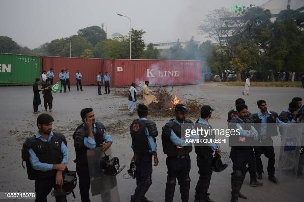 Pakistani riot policemen lineup on a blocked street leading to Pakistan's Supreme Court while Ahle Sunnat Wal Jamaat supporters a hardline religious...