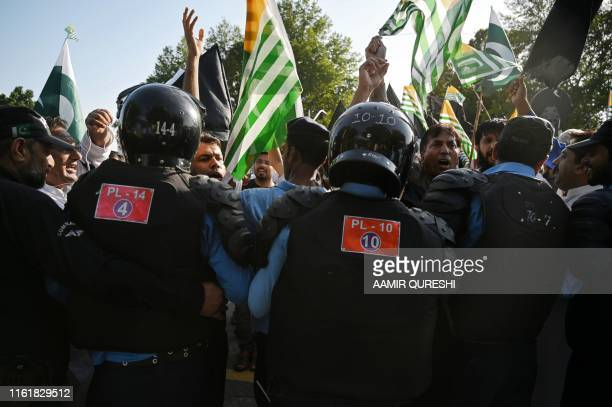 Pakistani riot policemen prevent protesters as they try to reach the Indian High Commission during a protest rally in Islamabad on August 15 as the...