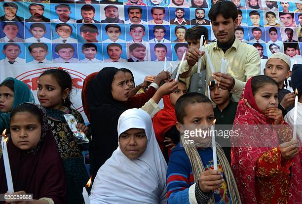 Pakistani school children light candles as they pay tribute to victims on the second anniversary of an attack on The Army Public School in the city...