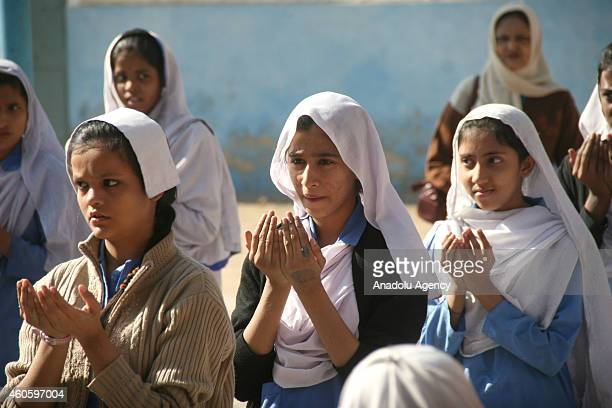 Pakistani school children pray for victims who were killed in a Taliban attack at the armyrun school in Peshawar during a memorial ceremony in their...