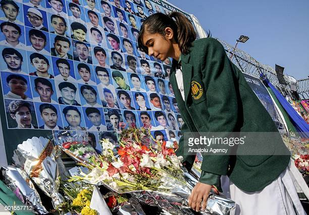 Pakistani schoolgirl lays flowers at a makeshift memorial for the victims of Taliban's deadliest attack at an Army Public School in Rawalpindi...