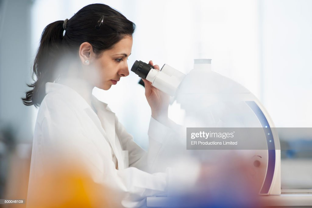 Pakistani scientist using microscope in lab : Stock Photo