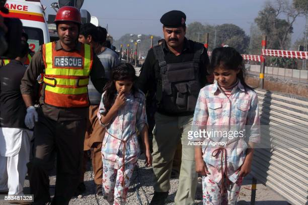 Pakistani security forces and rescuers escort girls who were evacuated Peshawar Agricultural Training Institute which was attacked by Taliban...
