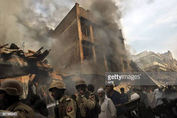 Pakistani security forces arrive to secure the site following a deadly car bomb blast at a market in Peshawar on October 28 2009 A huge car bomb...