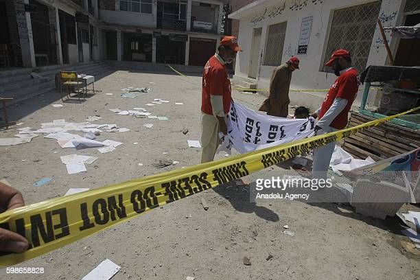 Pakistani security forces collect evidence after a suicide bomber attacked a court in the northern Pakistani city of Mardan killing at least 11...
