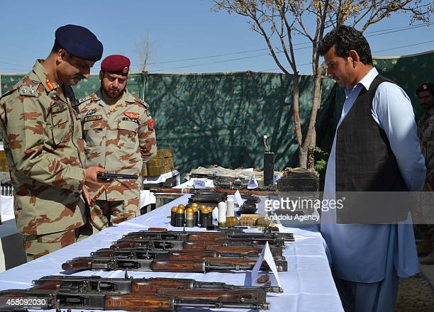 Pakistani security forces display arms and ammunition including suicide jackets captured after raids against militants in the Pakistani southwestern...