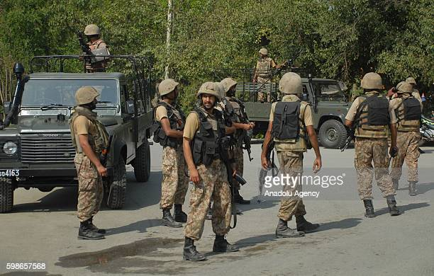 Pakistani security forces stand guard at a crime scene after four guntoting suicide bombers launched an attack on a Christian community housing...